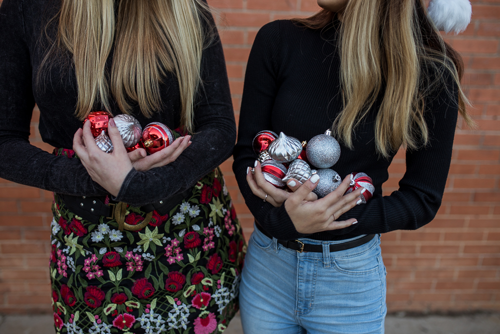 Friends photoshoot holding red and silver ornaments standing in front of brick wall in Downtown Buda. Photo by Erin Reas of Flying Lantern Photography.