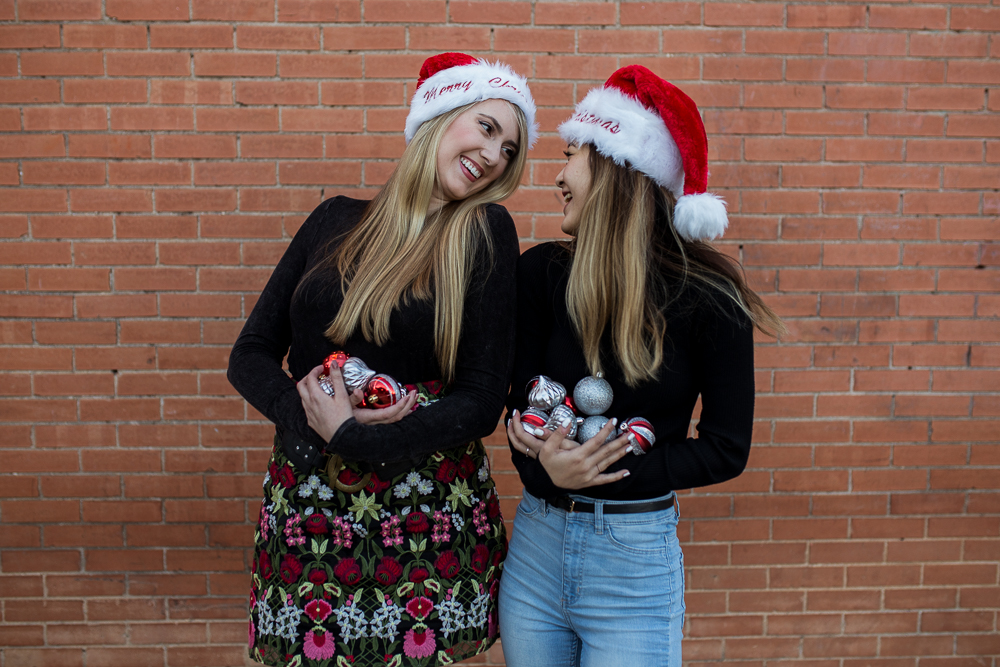 Friends photoshoot wearing Christmas Santa hats and holding red and silver ornaments standing in front of brick wall in Downtown Buda. Photo by Erin Reas of Flying Lantern Photography.