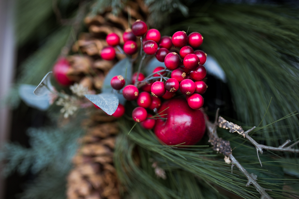 Winter berries in wreath with mini apple and pinecone. Detail photo by Erin Reas.