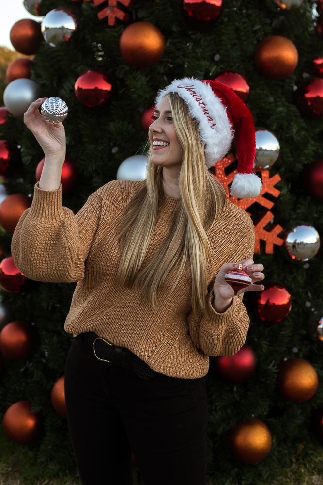 Girl lifestyle portrait wearing Santa hat and holding ornaments standing in front of Christmas tree in Downtown Buda. Photo by Erin Reas