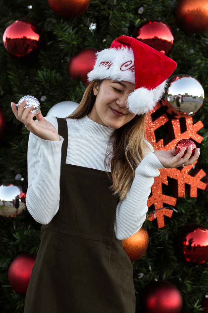 Girl lifestyle portrait wearing Santa hat and holding ornament in front of eye. Photo by Erin Reas