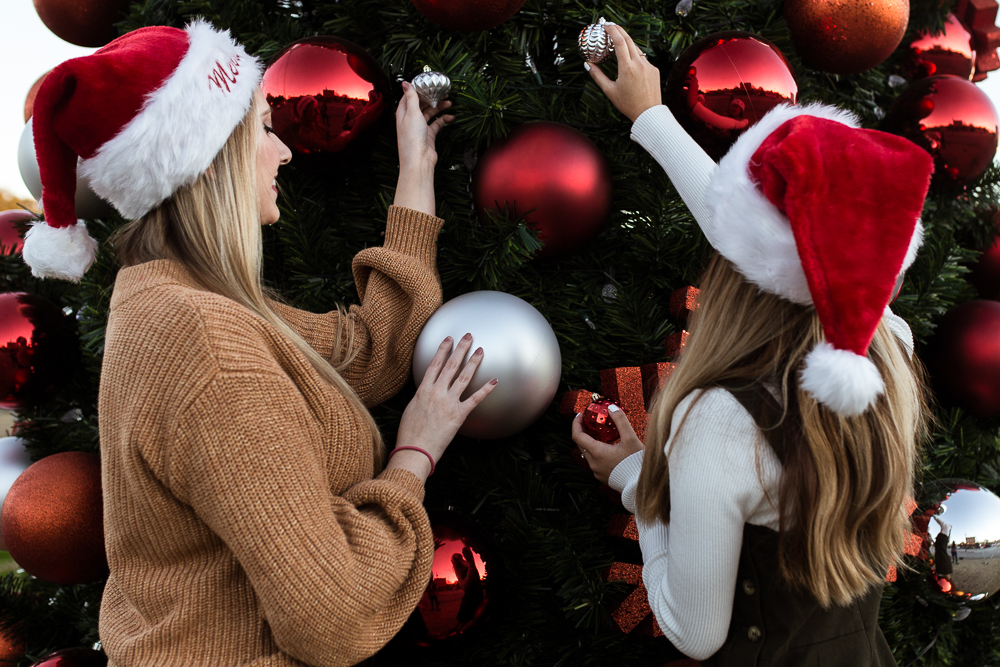 Friends portrait shoot in Downtown Buda, TX putting tiny ornaments against large ornaments in a giant tree. Photo by Erin Reas