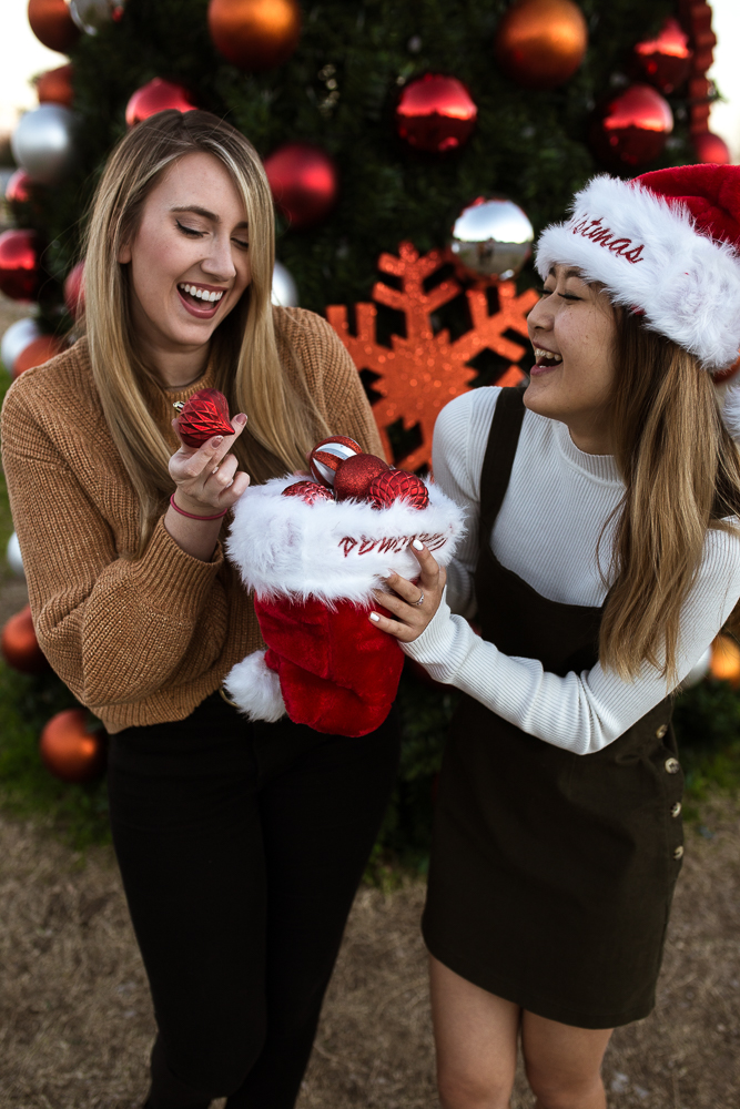 Two best friends holding santa hat filled with ornaments. Photo by Erin Reas photographer based in Austin, TX
