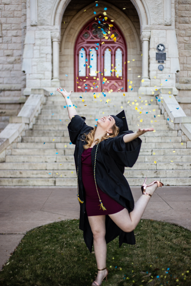 Senior portrait of girl at St. Edward's University in front of main building throwing confetti. Photo by Erin Reas Austin, TX photographer