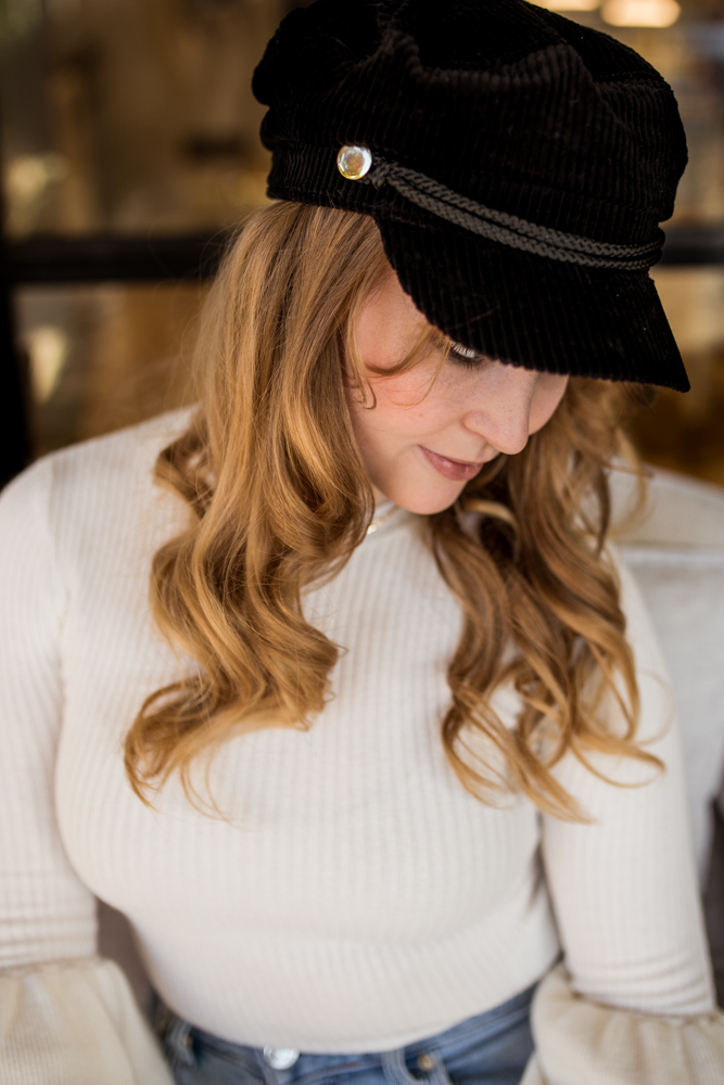 Girl senior portrait outside Kendra Scott wearing white sweater with bell sleeves and black newsboy cap. Photo by Erin Reas photographer in Austin, TX