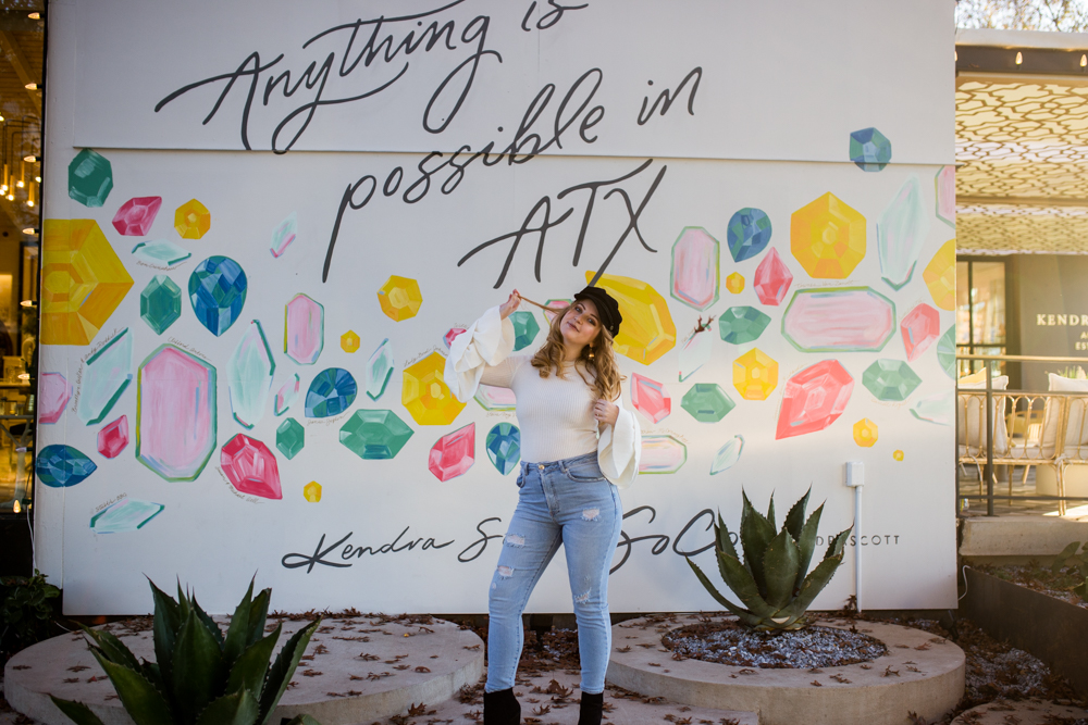 Girl senior portrait outside Kendra Scott wearing white sweater with bell sleeves and black newsboy cap in front of Anything is Possible mural. Photo by Erin Reas photographer in Austin, TX