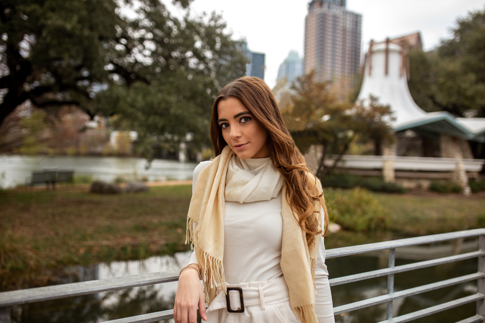 Lifestyle senior portrait at Auditorium Shores in Austin, Texas. Girl wearing white sweater and cream scarf. Photo by Erin Reas Austin area photographer