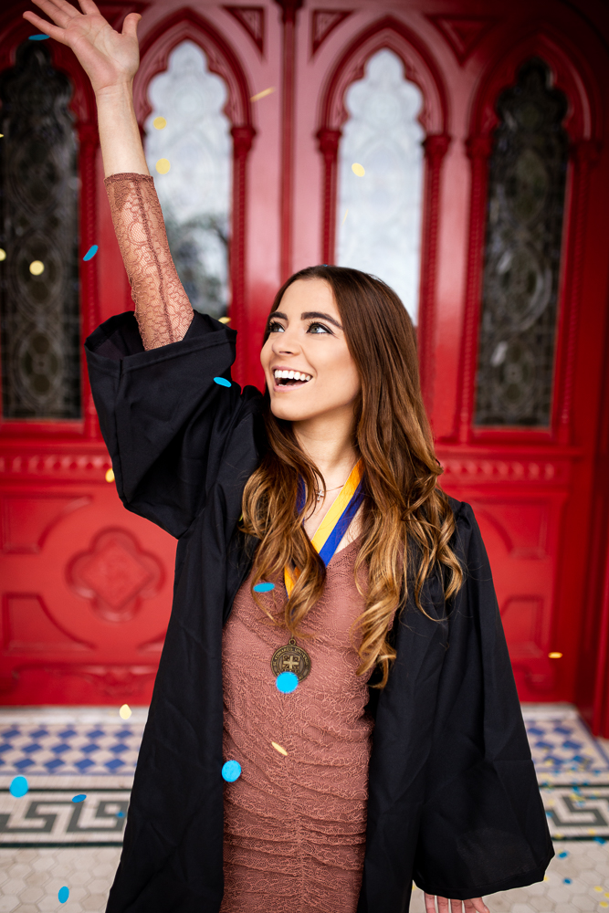 College graduate senior photo session at St. Edward's University in front of red doors. Graduate wearing cap and gown and throwing blue and yellow confetti. Photo by Erin Reas senior photographer in Austin, TX