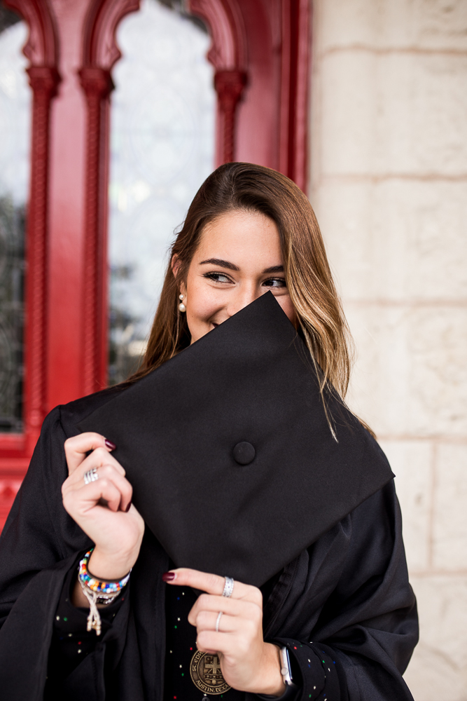 College graduate holding cap in front of face standing in front of red doors at St. Edward's University. Photo by Erin Reas senior photographer.