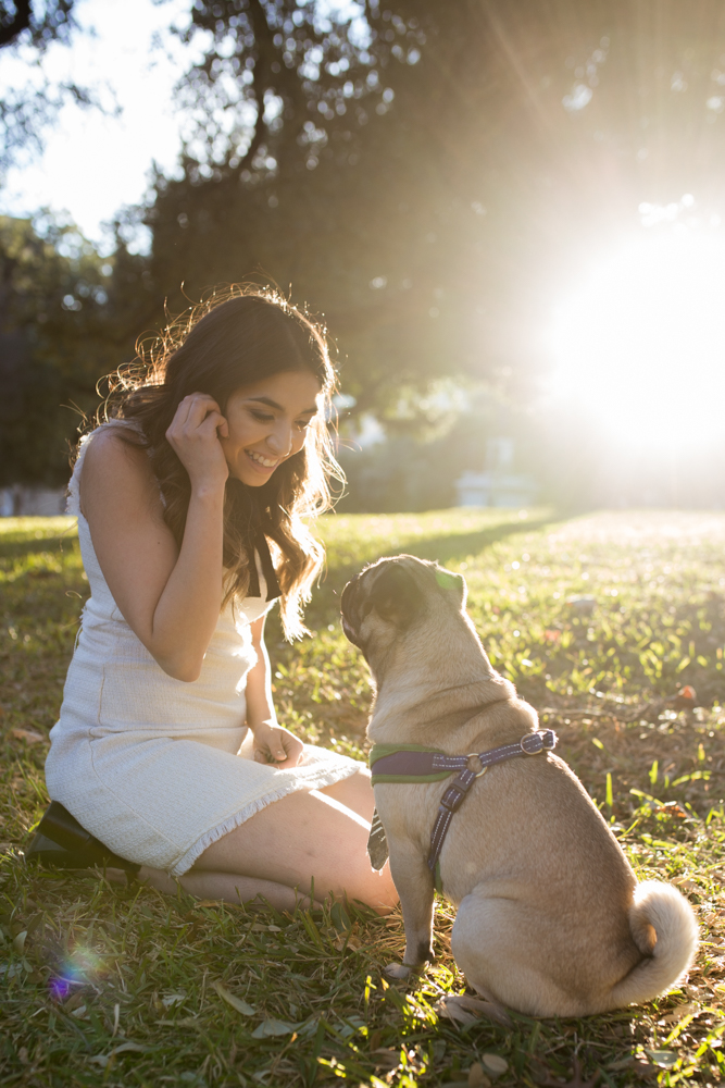 female college graduate sitting on lawn of texas state capitol with pug dog. photo by erin reas, austin photographer