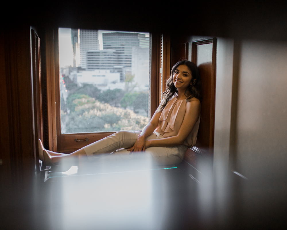 college graduate senior portrait in texas state capitol building. inside her office sitting next to window. photo by erin reas austin photographer