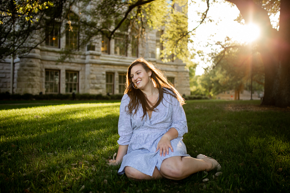 Female college graduate sitting on lawn wearing seersucker blue striped dress. Student at St. Edward's University. Photo by Erin Reas senior photographer in Austin, TX