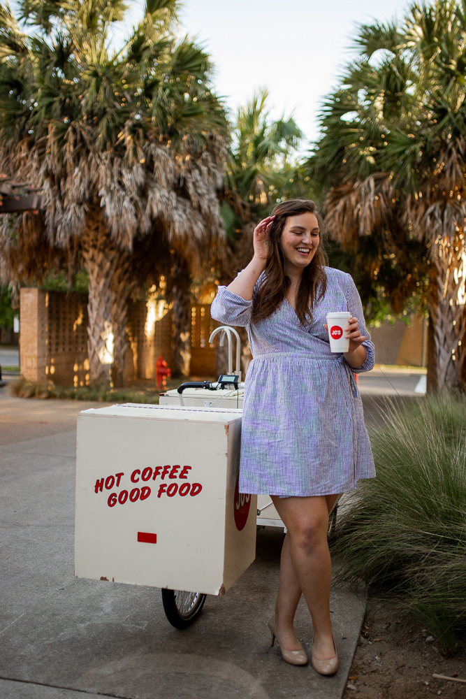 College senior at St. Edward's University holding Jo's coffee cup and standing next to coffee cart. Photo by Erin Reas senior photographer in Austin, TX.