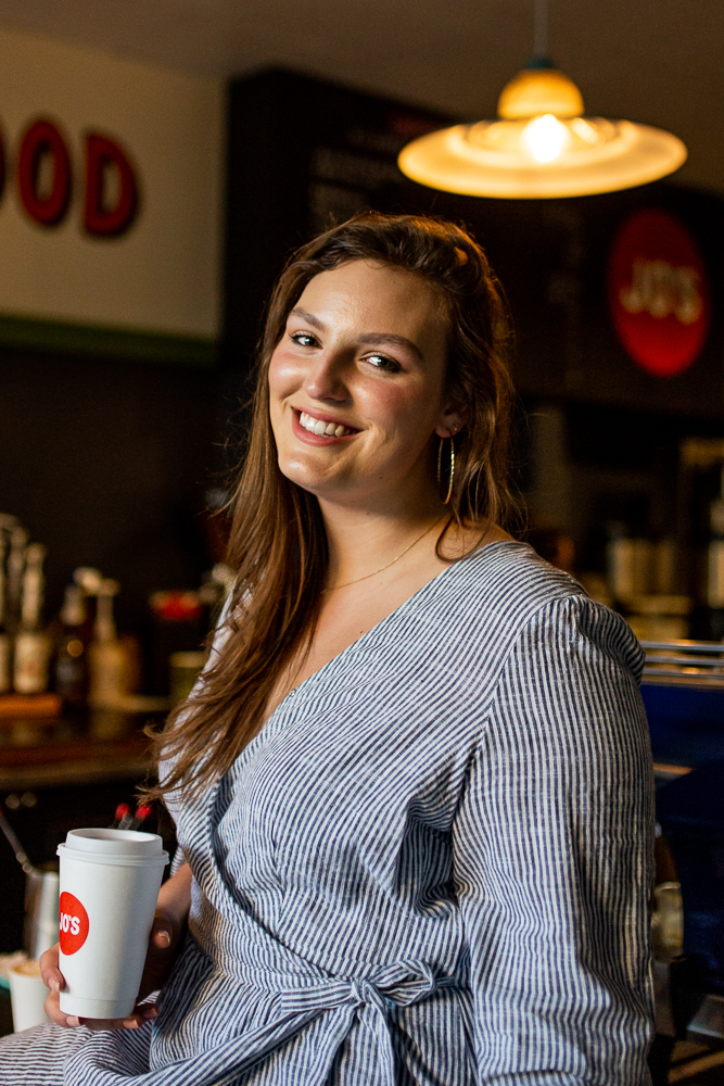 Female college student in Jo's coffee shop on St. Edward's University campus. Photo by Erin Reas senior photographer