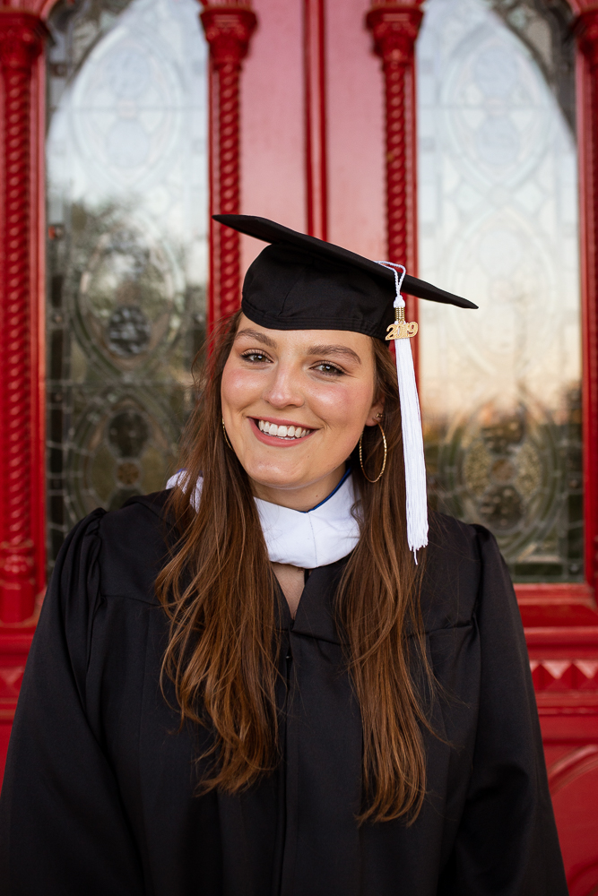 Female college senior standing in front of Red Doors of St. Edward's University. Photo by Erin Reas Austin, TX senior photographer.