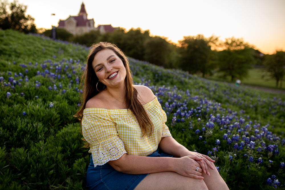 St. Edward's University college graduate sitting in field of bluebonnets wearing yellow check blouse. Photo by Erin Reas senior photographer in Austin, TX.