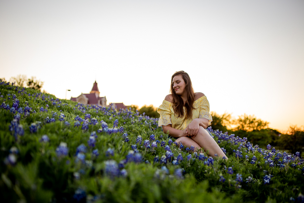 St. Edward's University college graduate sitting in field of bluebonnets wearing yellow check blouse. Photo by Erin Reas senior photographer in Austin, TX