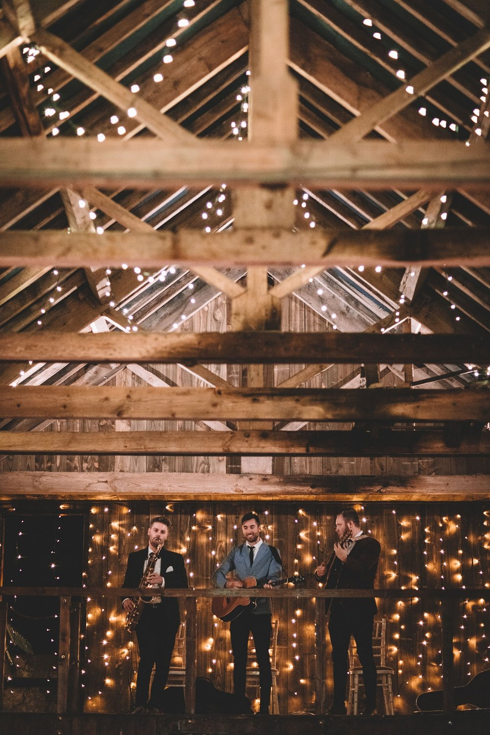 Rachel & Andrew by Lumiere Photographic - three bards play from on high in the Ceremony Barn.jpg