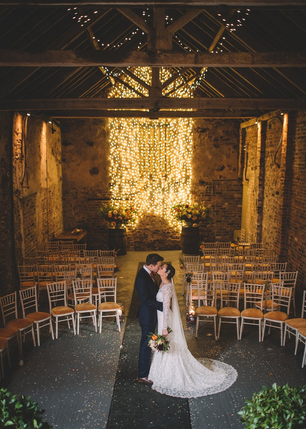 Rachel & Andrew by Lumiere Photographic - Rachel and Andrew steal a kiss in the Ceremony Barn.jpg