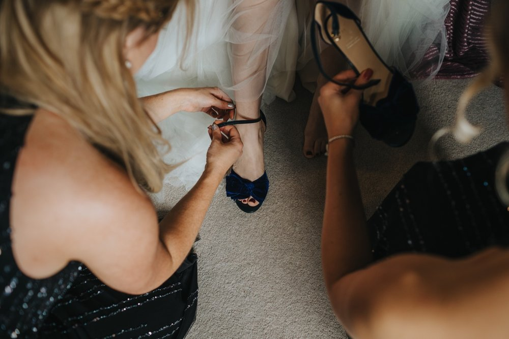 Sasha getting ready for her Big Day at The Normans with the help of her bridesmaids. Photo by Bloom Weddings
