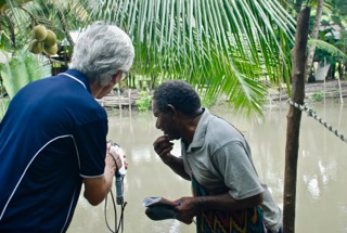 Martin Brezger conducts river water tests with a tribal leader.          PHOTO: Madeleine Brezger