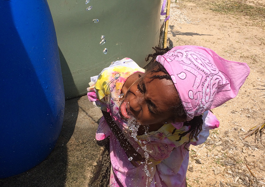 A local girl drinks fresh water straight from the source.jpg
