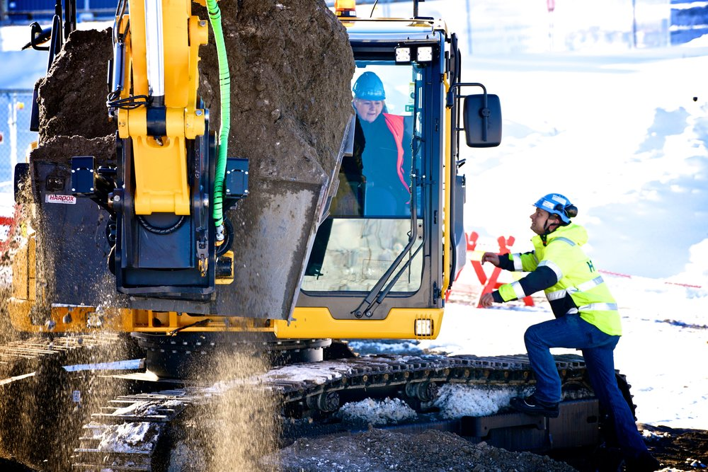 Statsminister Erna Solberg gjennomfører første spadetak til det som blir norges største universitetsbygg - med gravemaskin. Foto: Terje Heiestad/UiO