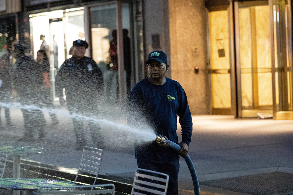 A worker power-washing the pedestrian plaza along Broadway in Manhattan's garment district.  Photo Credit: Jeenah Moon for The New York Times