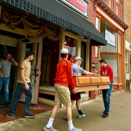 Volunteers help move furniture out of A Unique Flower & Gift Shop.