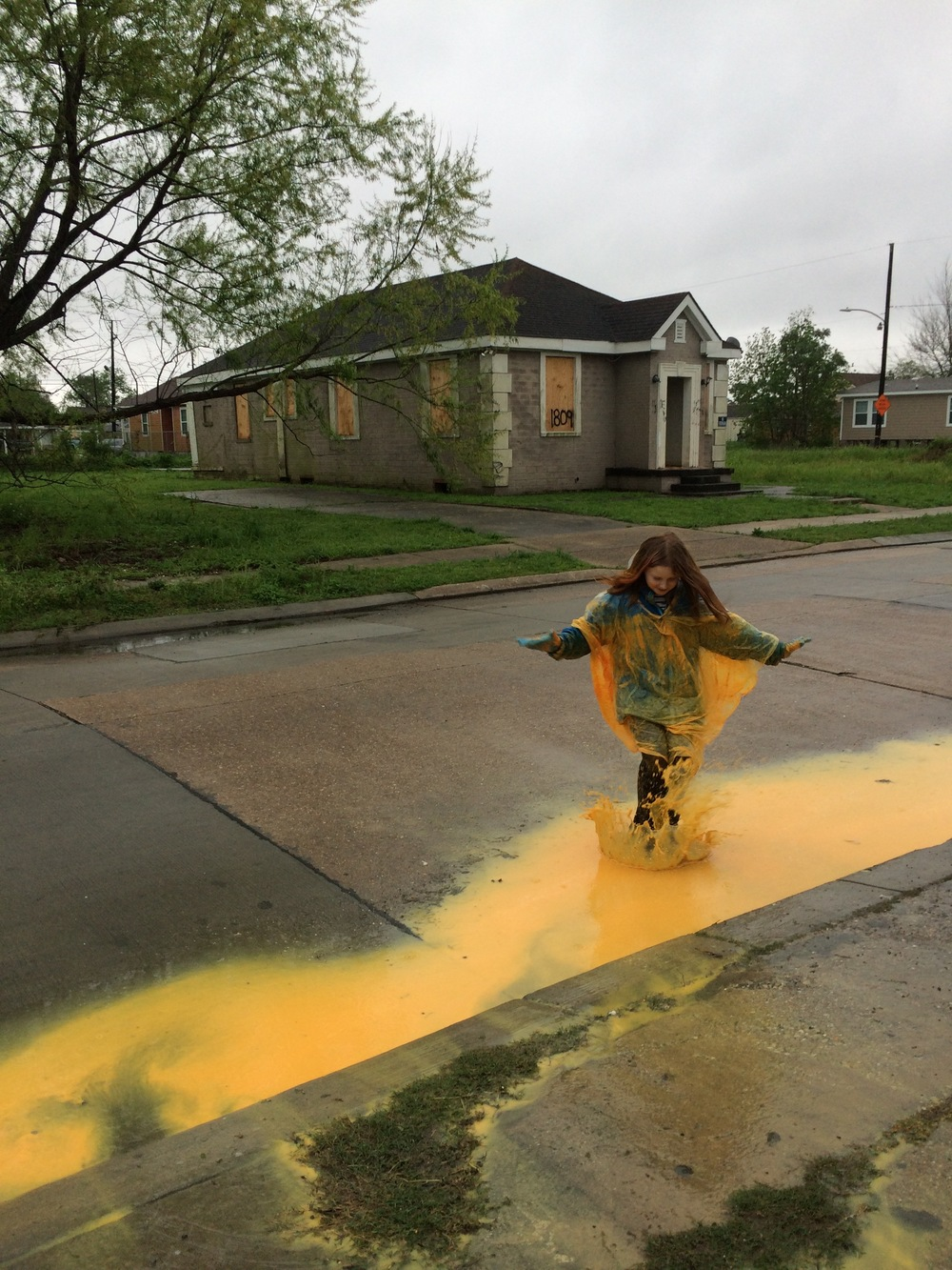 Charlotte, a volunteer from Chicago Sinai Congregation, jumps in a puddle made from the run-off of the farmhouse painting she and her crew did today.