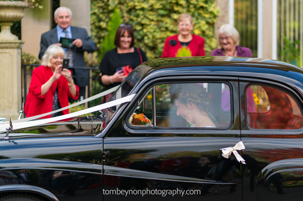 Guests photograph the bride and groom in their car