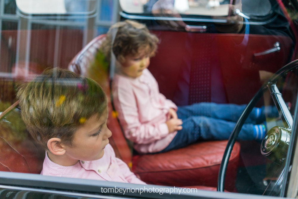 two small boys sit in the wedding car