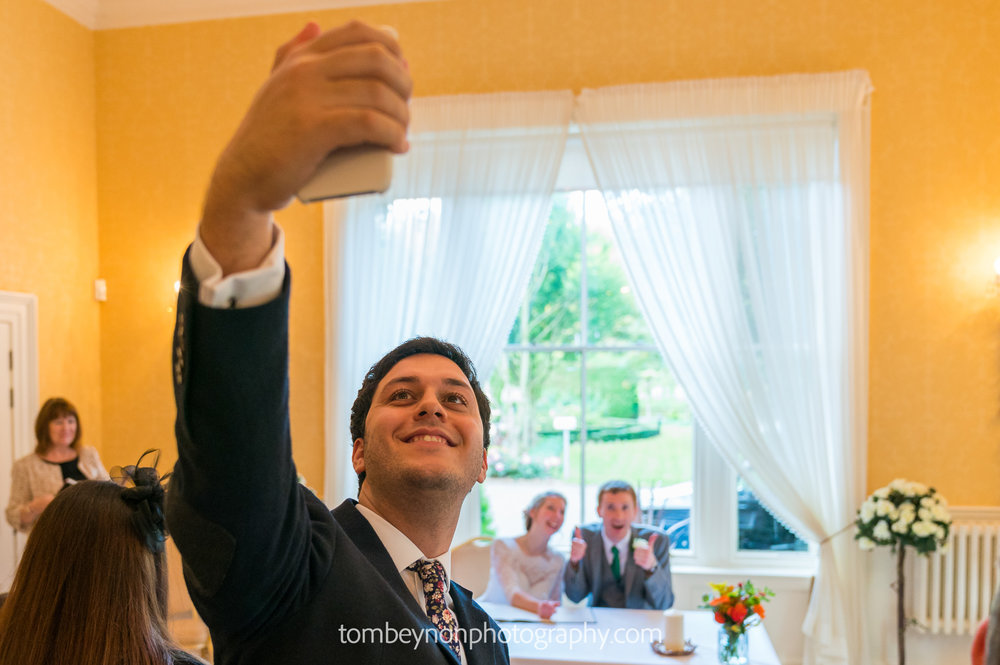 Guest takes selfie with bride and groom