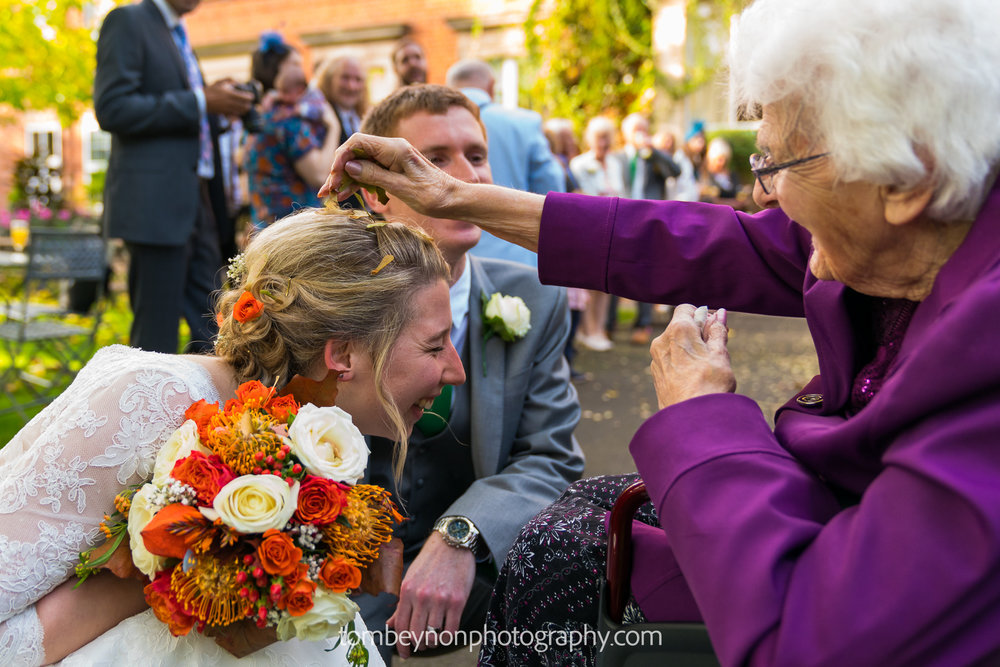 Bride kneels for confetti
