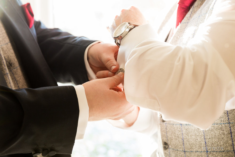Groomsmen put their cufflinks on