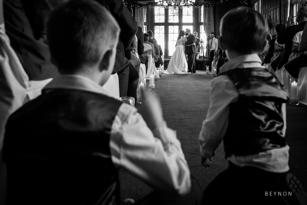 Two small boys watch the ceremony from the aisle