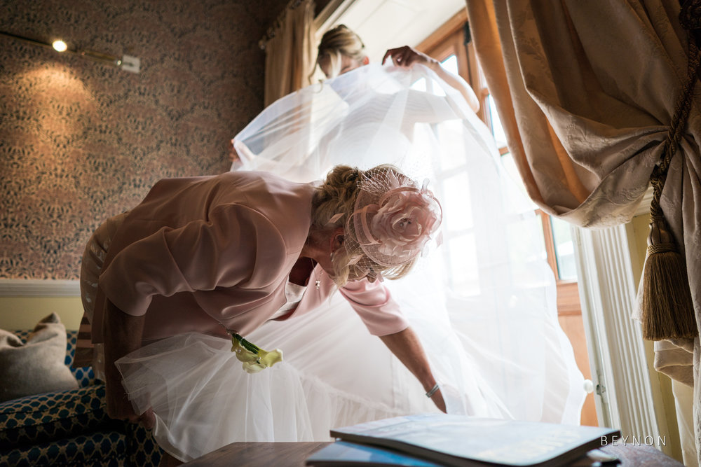 Mother of the bride helps fix the dress