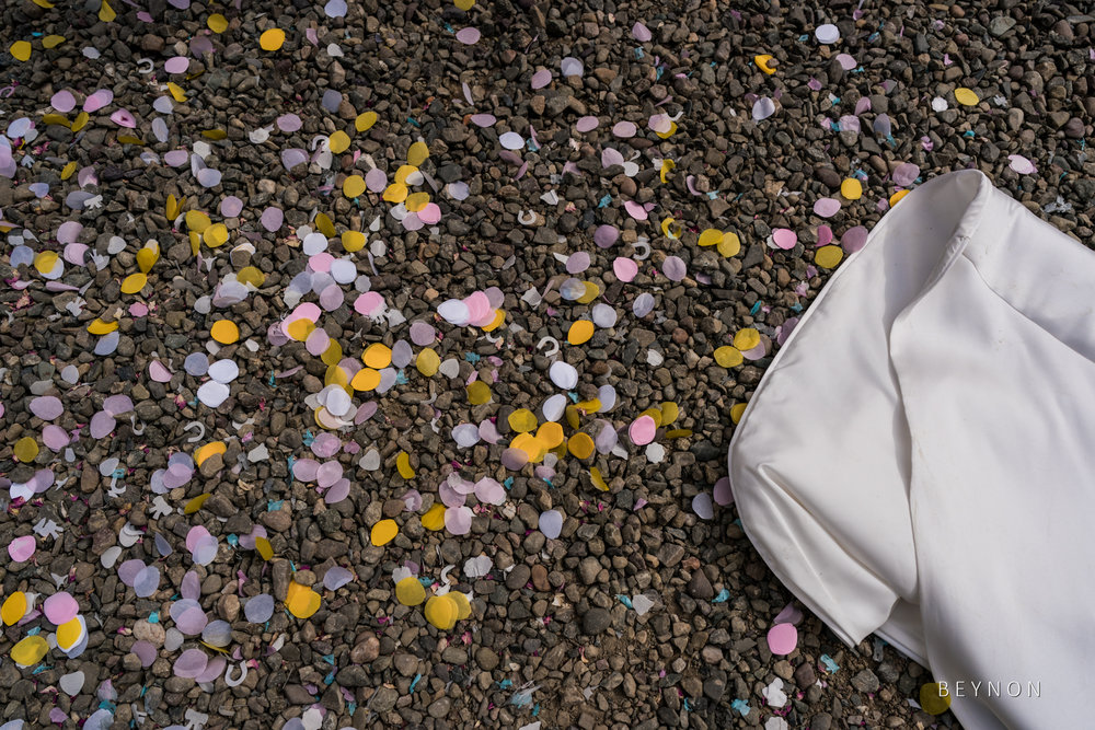 Confetti on the ground next to the bride's dress