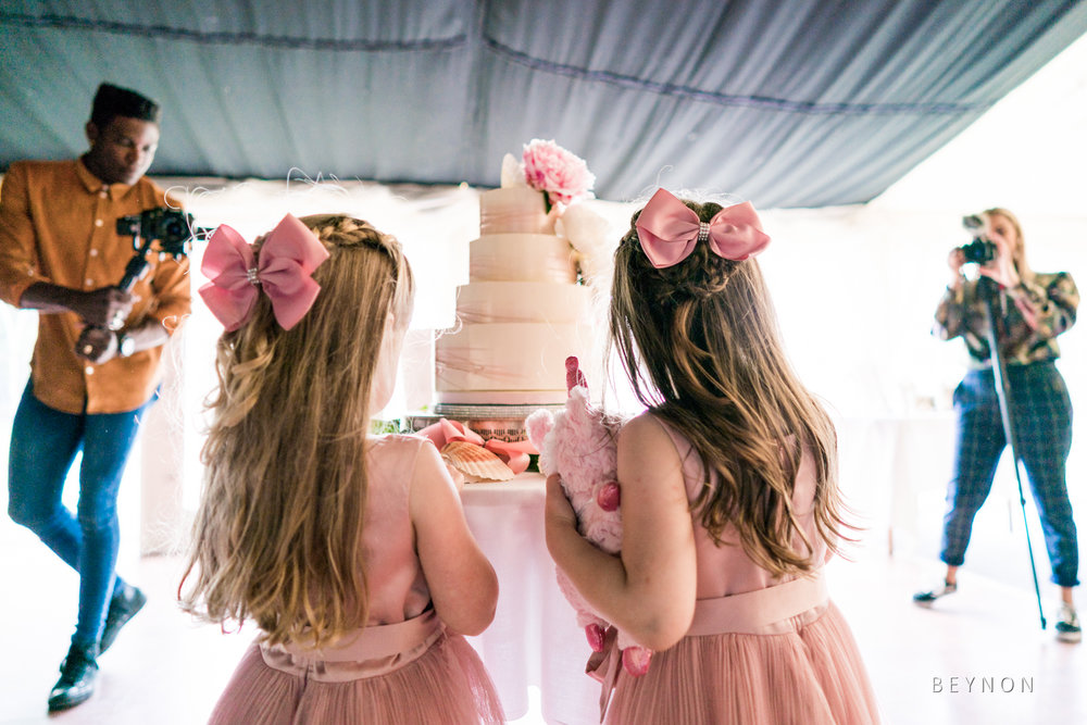 The flower girls look at the cake
