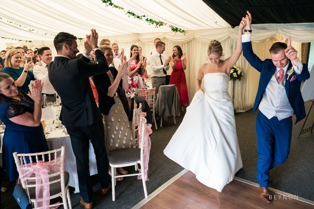 The bride and groom enter into the marquee