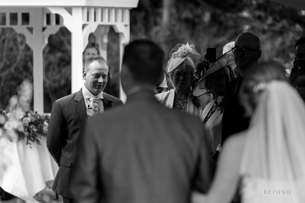 Groom looks at his bride as she walks down the aisle