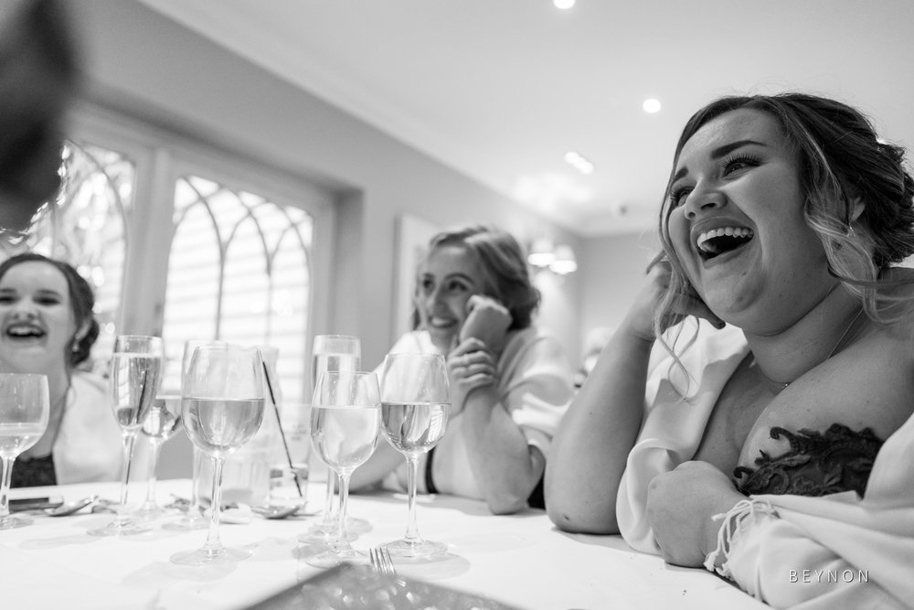 The bridesmaids laugh during the groom's speech