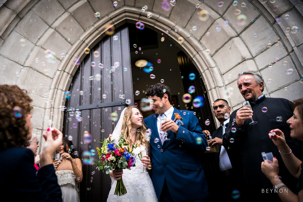 Guests blow bubbles as the married couple exit the church