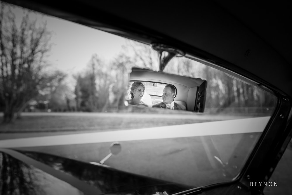 Image of bride and groom in car mirror