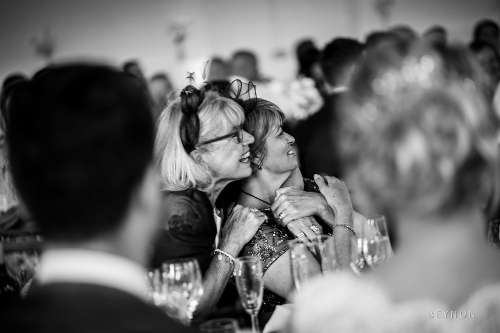 The mothers of the bride and groom hug during speeches