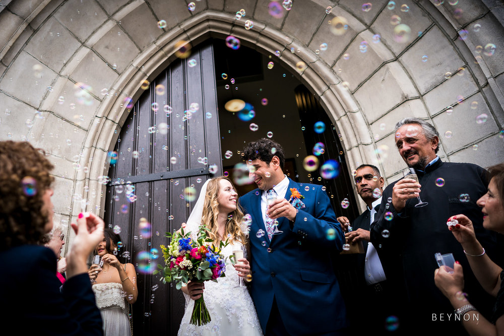 Bride and groom have bubbles blown over them