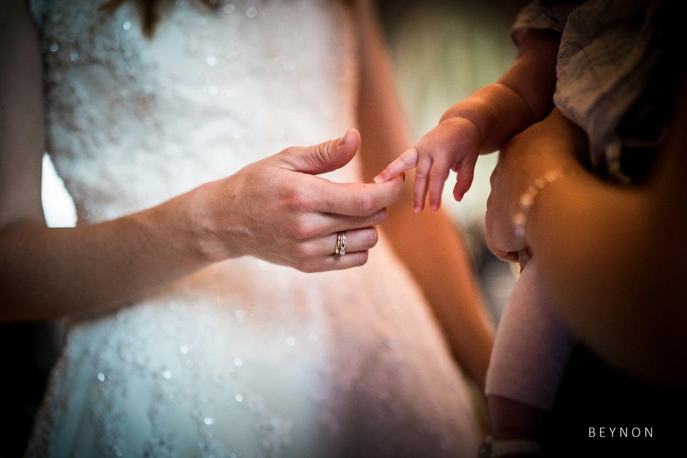 Bride holding a babies finger