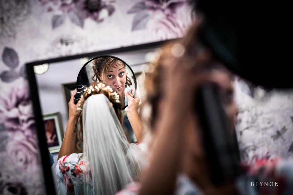Bride checks her veil in the mirror