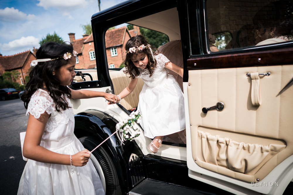 Flower girls help each other out of the wedding car