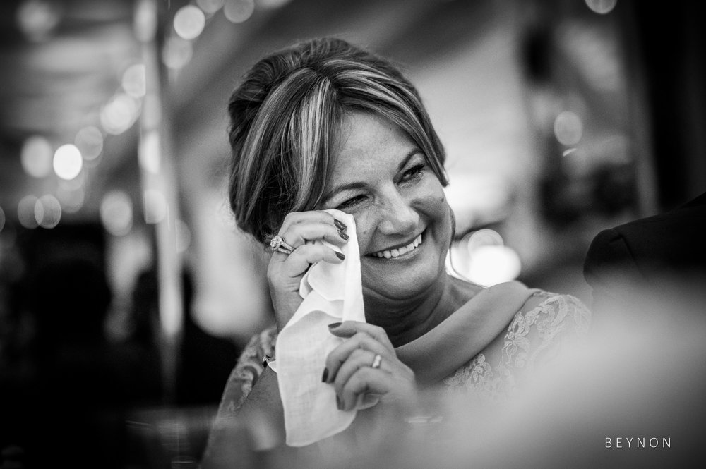 The bride's mother wipes away a tear